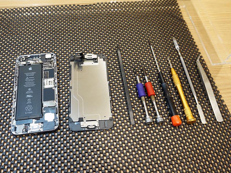 修理中のiPhoneと修理道具。