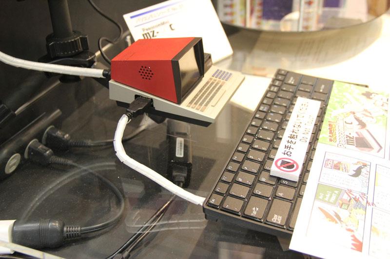 「PasocomMini」版MZ-80C実機へ、USBキーボードを接続。向かって正面左側にUSBポートが用意されており、そこへつなぐことになる。本体が小さいので、キーボードが巨大に見える?