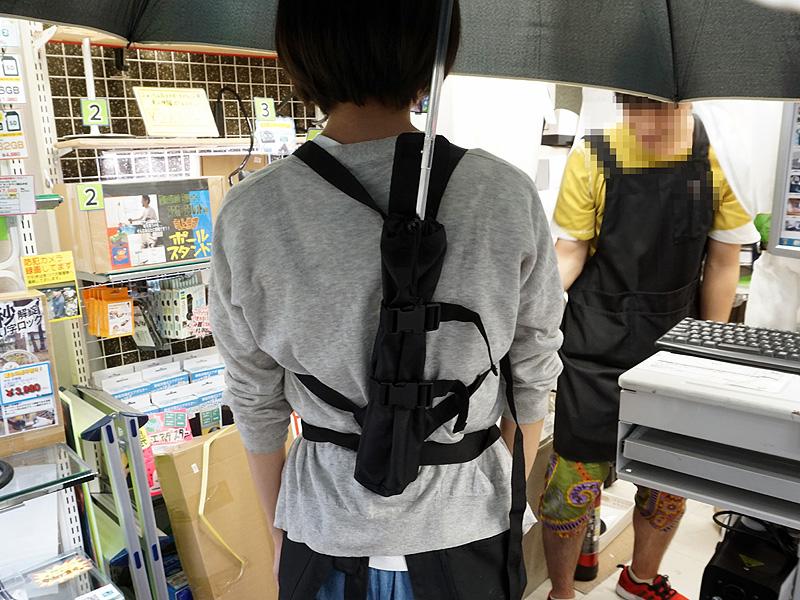 傘袋を背負い、その中に傘の柄の部分を入れる