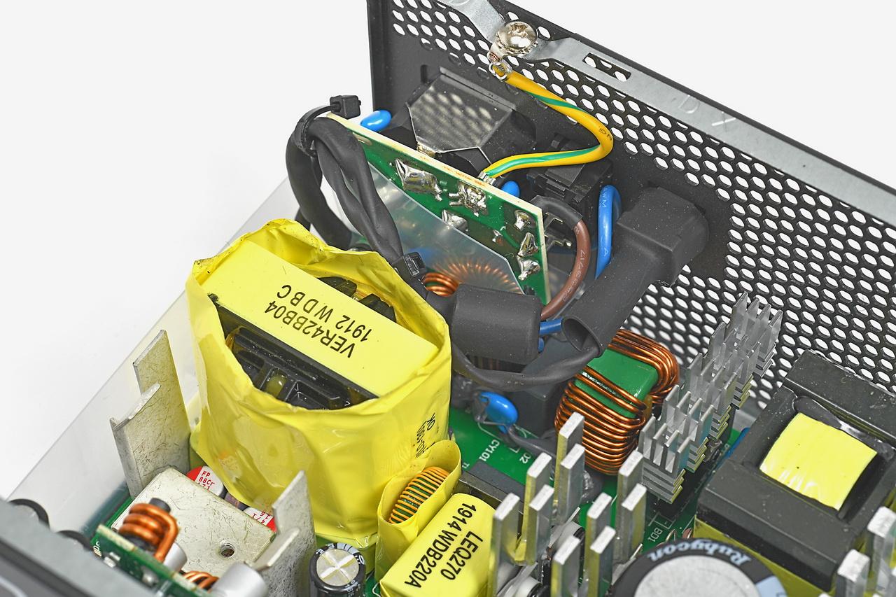 1次側のノイズリダクション回路をインレット裏に詰め込みトランスを実装。最近はやりの端よせトランスで奥行き14cmのショーティーを実現している。小型化しても2次側平滑のヒートシンクを設け放熱性を高めている