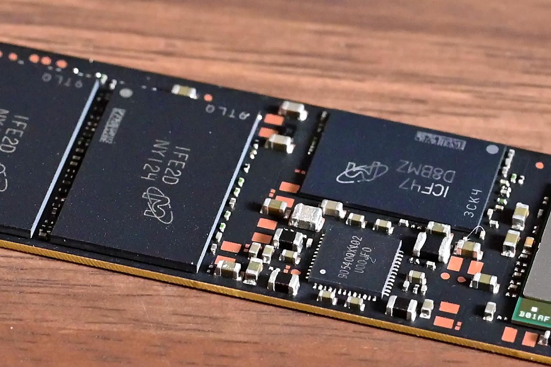 左側のチップはMicron製の3D NAND。176層の最新モデルと見られる。右奥のMicronロゴ入りのチップはキャッシュ用のDRAM