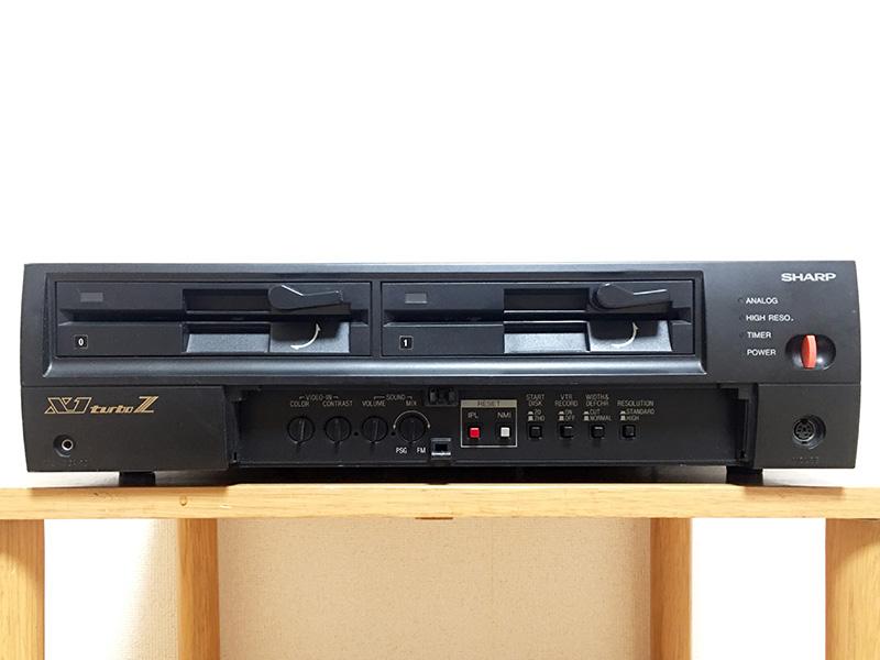 正面左下にはキーボード接続端子が位置していて、その上には黄金のX1turboZロゴがあります。蓋を開けると中には、取込み映像カラー調整つまみ、取込み映像コントラスト調整つまみ、音量調整つまみ、ミキシング調整つまみ、IPLリセットボタン、NMIリセットボタン、起動ディスクタイプ切り替えスイッチ、VTR録画モード切り替えスイッチ、200ライン自動切り替えストップスイッチ、標準/高解像度切り替えスイッチ、隣にマウスコネクタ、上部に電源スイッチが並んでいます。