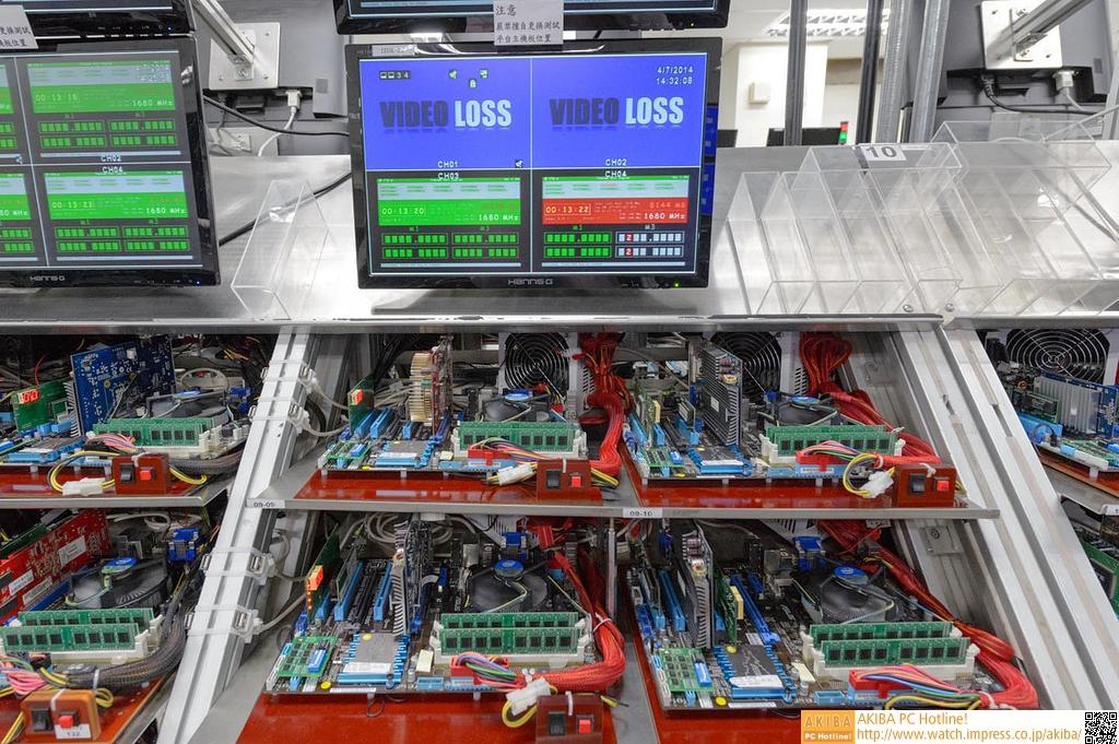 """<strong class="""""""">【実機で動作テスト】</strong><br class="""""""">動作テストは、実際にマザーボードに搭載する形で行われていた。もちろん専用のテストツールを実行するためだけのマシンだが、見慣れたマザーボードやビデオカードなど自作PCとしての一式がラックにまとめられ、それが両側に数十台、さらに全体で数百台並ぶ光景は圧巻だ。いわゆるMEMTEST的なテストが行われており、SPDに書き込まれた条件や、さらに少し上のクロックで動作していたりと、検査条件も単一ではなかった。"""