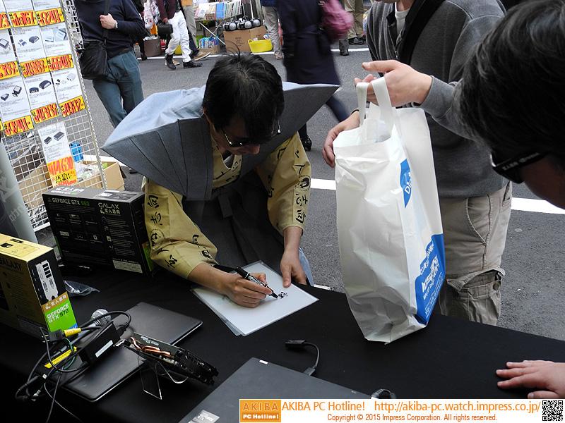 購入者にサインを書いている様子。