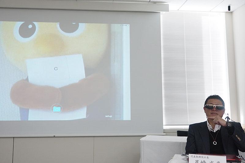 星崎社長が遠くにある人形を見て、視力4.0を実証(カメラで撮影された映像は左右が逆)