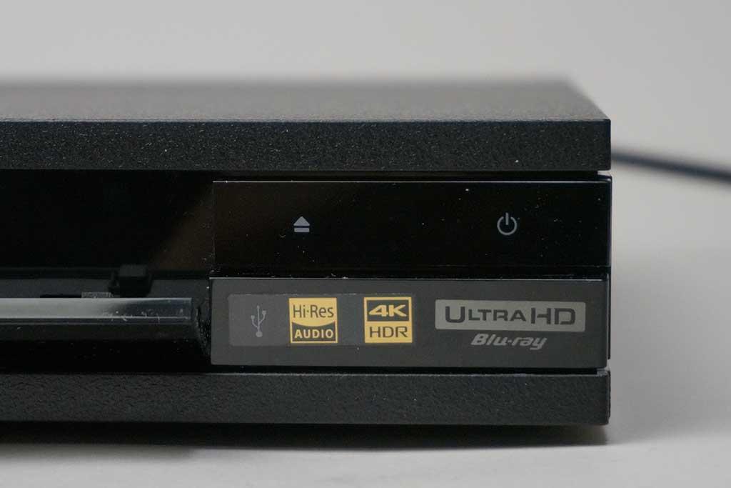 右側にある電源ボタンとディスク開閉ボタン。ハイレゾ対応ロゴ、4K/HDRロゴ、UHD BDロゴがある
