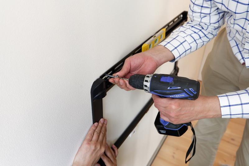 石膏ボードの壁にねじを回していく。奥にしっかりネジ留めできる下地があるかどうかが重要だ