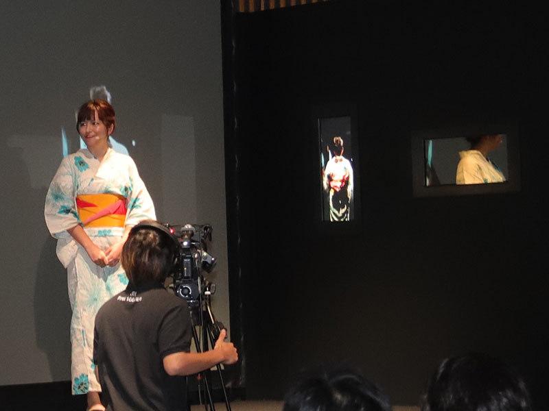 おくれ鏡のデモ。浴衣のモデル(左)が横を向いているが、おくれ鏡のディスプレイ(中央)は浴衣の後ろ姿を鏡に映していた数秒前の映像が表示されている