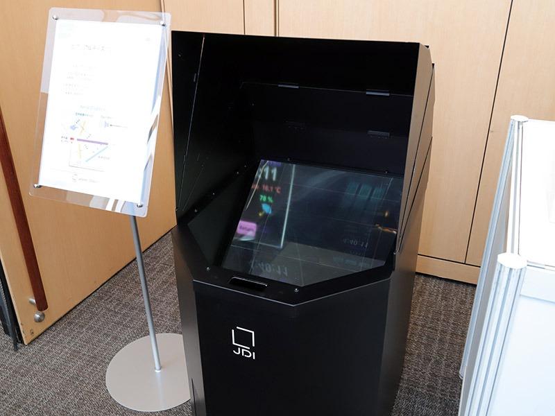 センサーで指の動きを読み取ってタッチ操作できる、空中結像ディスプレイの展示。フルHDディスプレイとハーフミラーを搭載。新開発の再帰性反射フィルムで解像度と輝度を高めたという