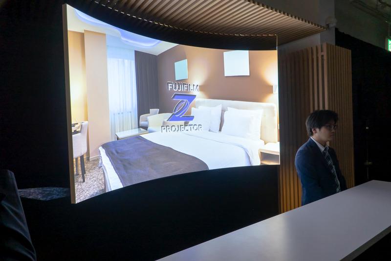 ホテルフロントでの使用例。プロジェクターはカウンターのテーブル内に格納。短焦点投射のため、従業員が受付にいても映像に被りにくいという