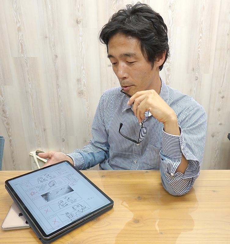 実際に絵コンテなどの作業をする様子を再現する佐藤監督。「GEMBA Note」にペンでアイデアやシーンの様子を書き込み、修正しながら撮影を進めている