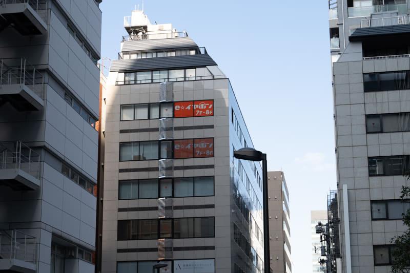 正面のビルの窓に見える、オレンジ色の看板が目印だ