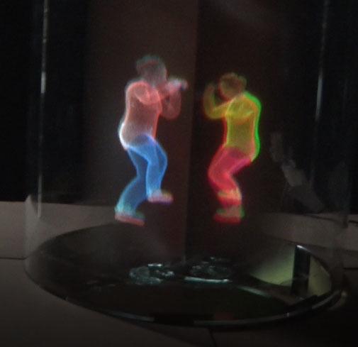 試作機の表示。中央に黒い棒のようなものが見えるが、これは映像が見えにくい部分が黒くなっているだけで、実際に棒があるわけではない。下の映像は格闘ゲームをイメージしたもの