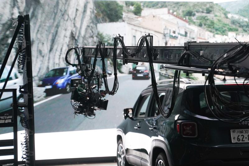 助手席の女性にフォーカスしながら、車外のカメラが回り込むように撮影。助手席のガラスに、街並みが写り込んでいるのがわかる