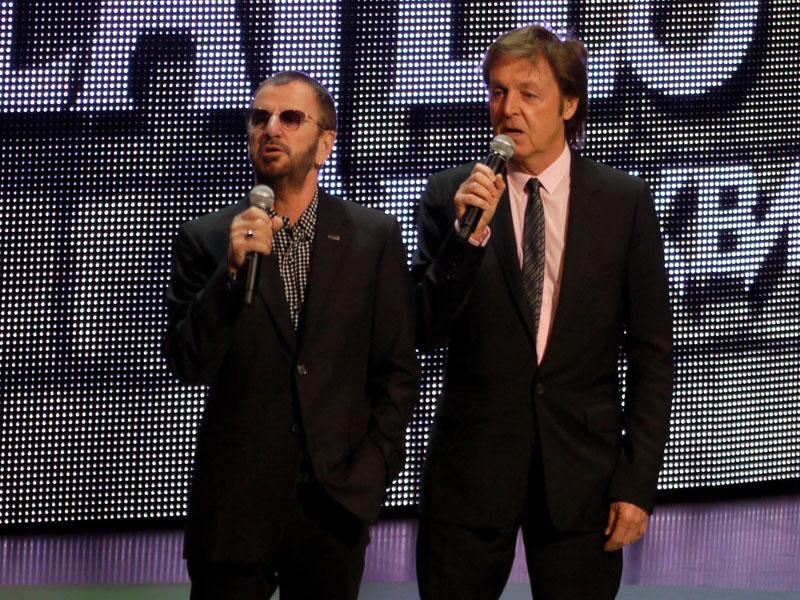 """リンゴ・スターとポール・マッカートニーが並んで壇上に。""""登場できる""""ビートルズ・メンバーは全員が来場したことになる、自らエアギターをして、おどけてみせる一幕も"""