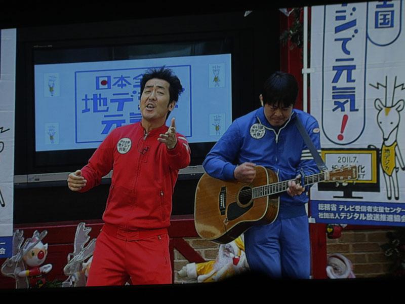 """「地デジ芸人」のテツandトモと、「地デジで元気娘」の2人による、岩手県盛岡市でのイベント会場からの中継も。テツandトモは、「あずさ2号」の替え歌で""""2011年7月24日からテレビはテレビはアナログから旅立ちます~""""と熱唱"""