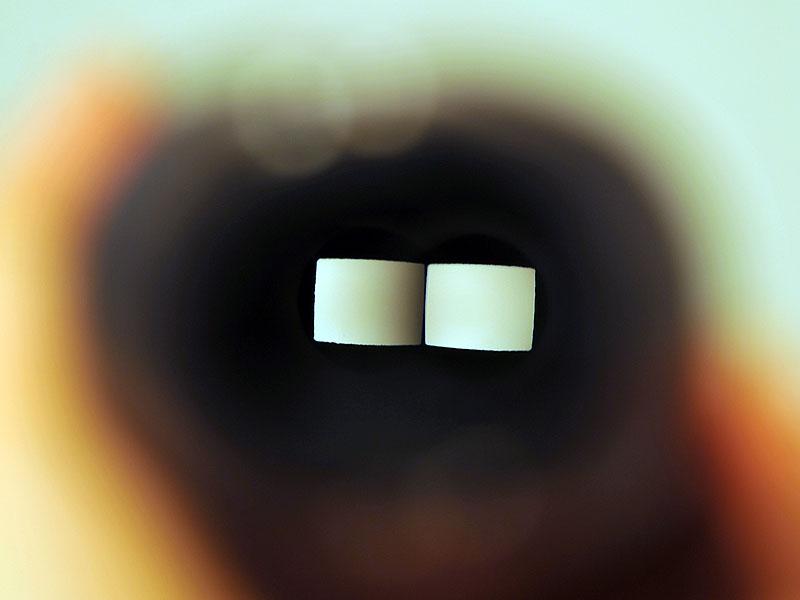 <FONT size=2>背面から、前面の穴にフォーカスを合わせたところ。前面のレンズの穴が四角形なのがわかる</FONT>