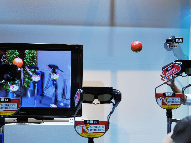 <FONT size=2>糸で吊るしたリンゴを振り子のように動かし、カメラに近づけたり、離したりしながら撮影。立体視を確認できるデモ</FONT>