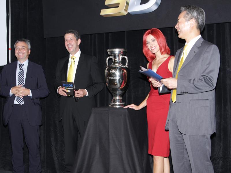 UEFAのデビッド・テイラー氏(左)と、Sharp Electronics Germany/Austria社長のフランク・ボルテン氏(左から2番目)、ミス IFA(右から2番目)、佐々岡氏で、UEFAの優勝カップを囲んで撮影