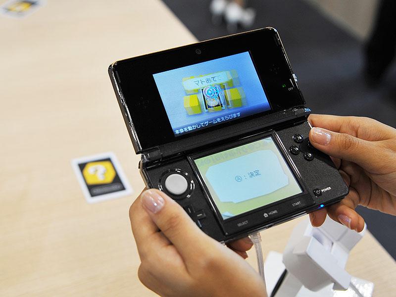 <FONT size=2>ARゲームズをプレイ中。机の上の黄色いマークに反応し、現実には存在しない的がゲーム画面には現れる</FONT>
