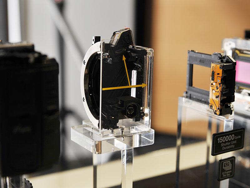 <FONT size=2>α77の分解展示。中央にあるのがミラー部分。透過タイプとなっており、反射した光を上部のAFユニットに送り、透過した光がセンサー(右の写真)に届く</FONT>