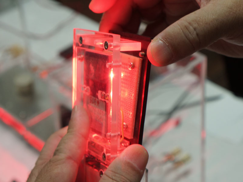 """香川大学工学部のブースでは、世界初という""""光アンプ""""を展示。通常のアンプはトランジスタやIC、真空管などの増幅素子が使われるが、発光ダイオード(LED)とフォトダイオード(光センサー)から作られた増幅素子「ダイスター(distar)を発明・採用しているのが特徴。岡本研正教授の発明で、原理としては、LEDの光をフォトダイオードで受け、太陽電池のように発電。その電気を戻してLEDの発光をさらに強くし、その光で発電……というサイクルを繰り返して増幅するという。ブースでは光を遮ると音が出なくなるなど、試作アンプから実際に音を出して原理を説明している"""