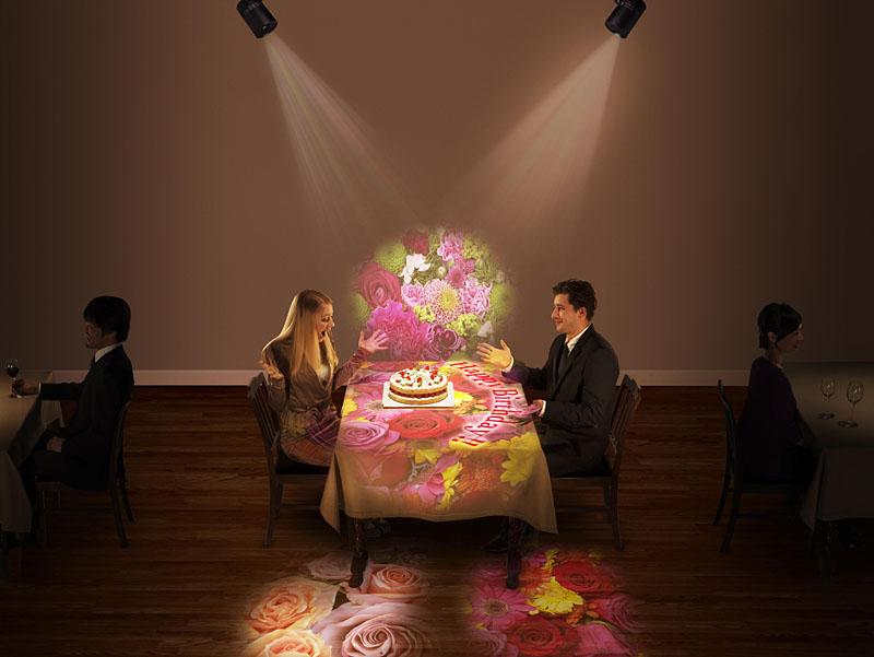 飲食店のテーブルクロスに絵柄を投写したイメージ。映像や商品説明など、様々なデータを投写できる