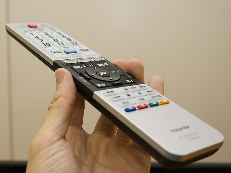 薄型デザインのリモコン。十字キーやダイレクト選局用の12キーなど、ボタンに角度がつけてあり、操作がしやすいように配慮されている