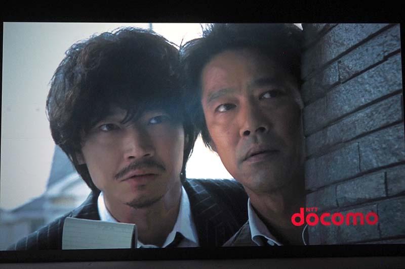 """新CMのワンシーン。""""得ダネ""""を追う堤さんと綾野さんが至近距離で同じ方向を見つめている"""