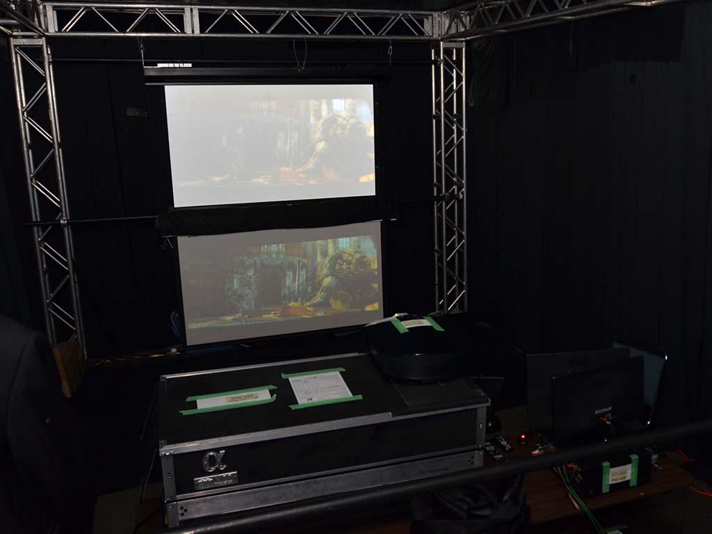 デモの様子。巨大なケースのような機材がMTTが試作したHDRプロジェクタ。その上に乗っているのがソニー製の民生向けSXRDプロジェクタ(型番確認できず)。このSXRDプロジェクタの映像にHDR表現部分を上乗せ投射する形でのデモを行っていた。下の映像はもう一基用意されていた同型番のSXRDプロジェクタの映像
