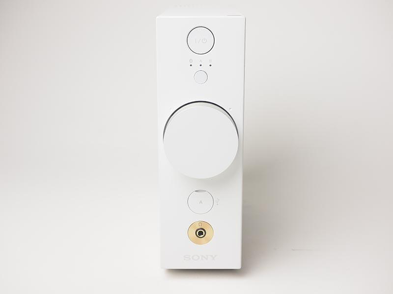 本体部の正面。上部に電源ボタン、入力切り替えボタンとインジケーターがあり、中央に大きなボリュームがある。下部にはUSB端子とヘッドフォン出力がある