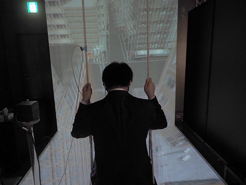"""昨年、VRでの「<a href=""""http://av.watch.impress.co.jp/docs/news/20141023_672821.html"""" class=""""n"""" target=""""_blank"""">お医者さんごっこ</a>」を出展したソリッドレイ研究所は、3Dプロジェクタ映像を用いた「飛翔体験」をデモ。ブランコに座って3Dメガネをかけて体験する。このブランコはただ吊るされていて動かないが、映像では大きなビルとビルの間を高速でブランコが動くため、思わず体に力が入ってしまう"""