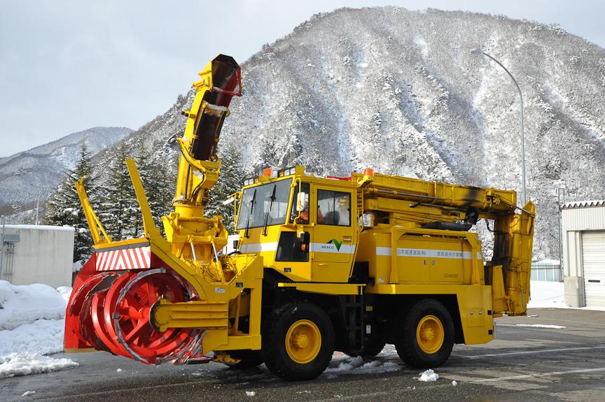 ロータリー除雪車。車体前面のロータリーを回転させて雪をかき込み、車体上部の排出口から飛ばす。排出口は折りたたみ式になっている。後方に折りたたんだコンベアで追走するダンプに雪を積みながら査証することもできる。ロータリー部分は2軸構成