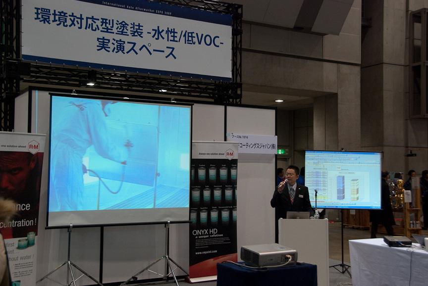 環境対応型塗装・水性低VOC-実演スペースでのプレゼンテーション。大きなスクリーンに映し出されているのは、塗装ブースでの作業の模様