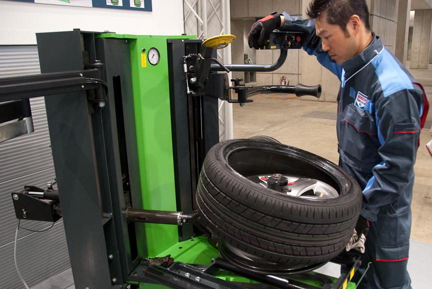 最新式のタイヤチェンジャー「TCE 4530」。これはランフラットタイヤの取り外しデモ。右手下にあるコントロールボックスで、ホイールへと伸びるアームのコントロールを行っている。タイヤレバーをまったく使わずに作業可能