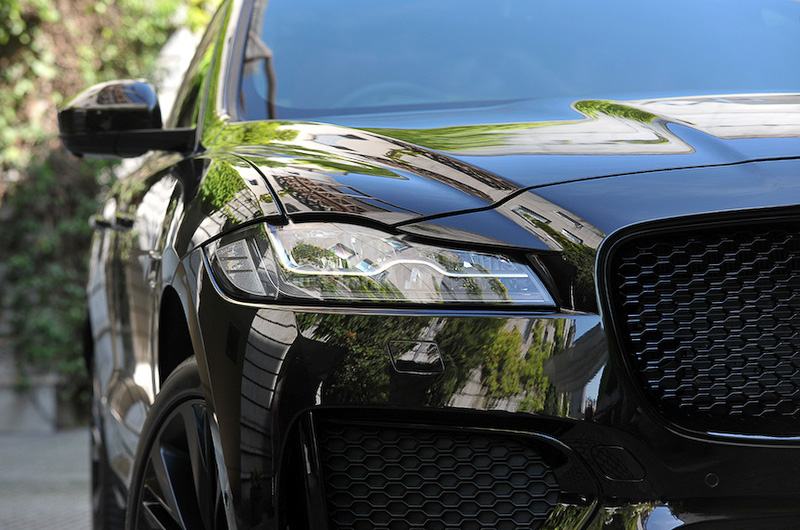 """80%にアルミニウムを使用するという軽量モノコック車体構造のF-PACE。空力性能にもこだわり、Cd値は0.34とした。エクステリアではグリルのアッパーラインとヘッドライトのエッジラインを結ぶことで「鋭い目つき」を演出するほか、サイドラインは後方にいくについれて傾斜を持たせ、前へと進む疾走感を表現。撮影車はオプション設定の""""J""""ブレードシグネチャーLEDライト付アダプティブLEDヘッドライトを装備する"""