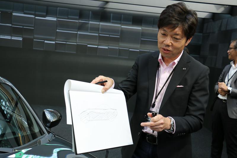 マツダ株式会社 商品本部 主査 兼 デザイン本部チーフデザイナー 中山雅氏。デザイナーとして活躍してきた中山氏だけに、その場でスケッチボードにイラストを描きながらファストバックスタイルを得た新しいロードスターについて説明を行なった