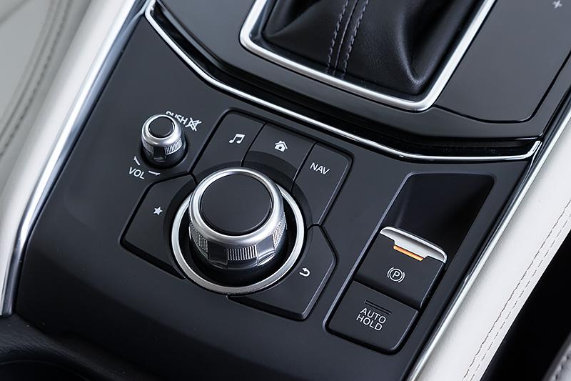 シフトセレクター後方にマツダコネクトのインターフェイスと電動パーキングブレーキのスイッチをレイアウト。電動パーキングブレーキにはホールド機能も付く