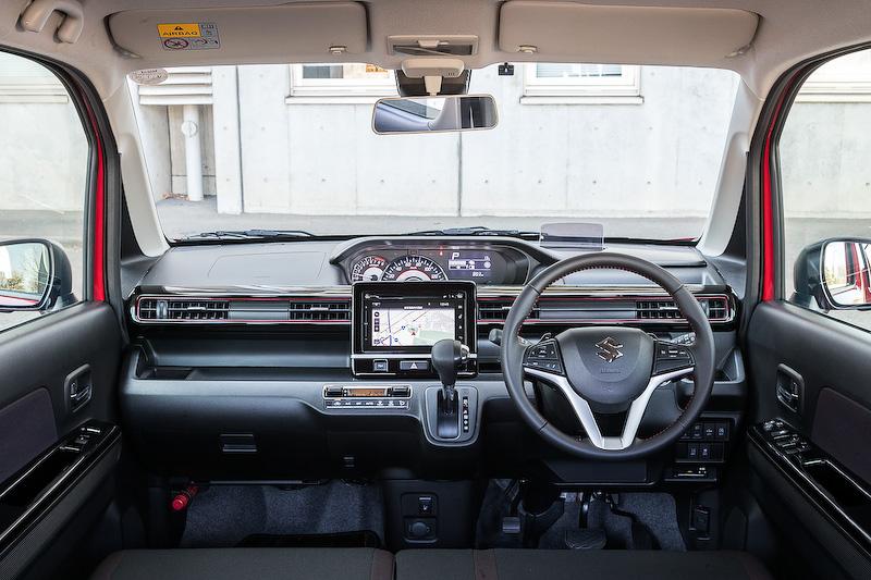 新型ワゴンRシリーズでは新プラットフォーム「HEARTECT」の採用により室内長2450mmの広々空間を実現するとともに、Aピラーのスリム化やドアミラーの小型化および下方に配置することで右左折時の視界を確保。写真はブラックを基調にしたワゴンRスティングレーのインテリアで、エアコンルーバーガーニッシュに赤いアクセントが入るのが特徴的。ヘッドアップディスプレイは標準装備される