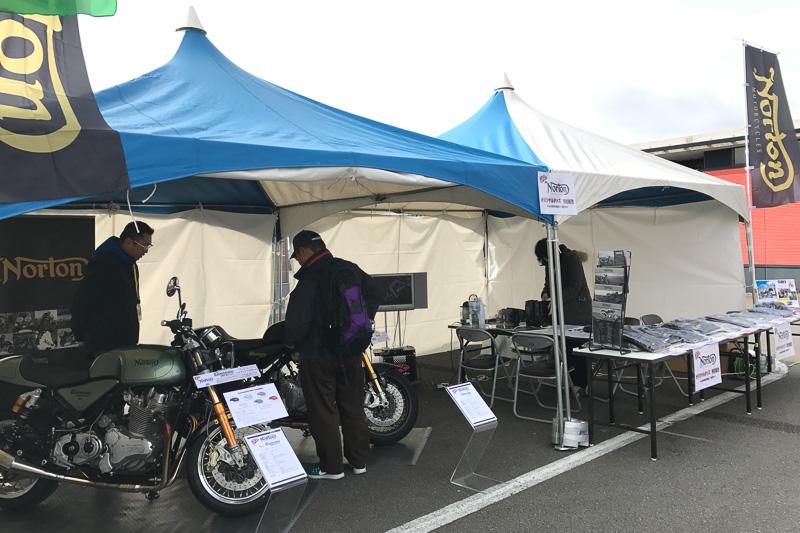 """英国の「Norton Motorcycles」を日本に輸入しているPCIは、""""新しいのにクラシカル""""なNortonのバイク2台とオリジナルグッズを展示&販売。「歴史と伝統ある英国の4輪がロータスなら、2輪はNorton。ロータスオーナーにもNortonライダーが意外と多いのは、ともに通ずる魅力があるのでしょう」と、ステージ上でのPRタイムで解説してくれました"""