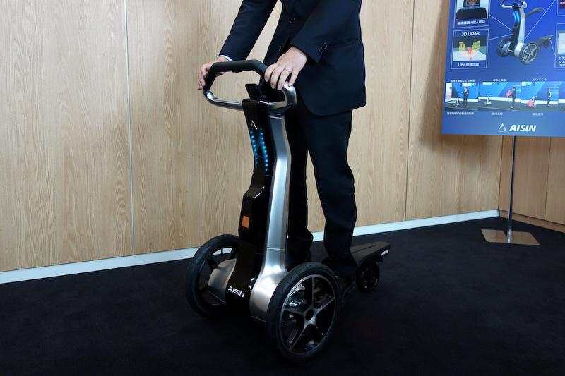 「でかけよう、冒険しよう、広がる世界、つながる社会」をコンセプトに掲げる3輪パーソナルモビリティ「ILY-Ai」。「Carry Mode」「Kick Scooter Mode」「Vehicle Mode」「Cart Mode」の4つのモードに可変するとともに、3D LiDARや2D LiDARを用いて知能化し、危険を察知して止まったり、呼ぶと来るといった自律走行、人の後ろをついてくる追従走行などを行なえるのが特徴になる