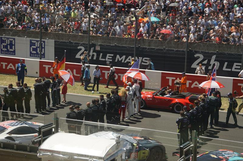 ドライバー、メカニックが整列している中、トロフィーが進んでいく