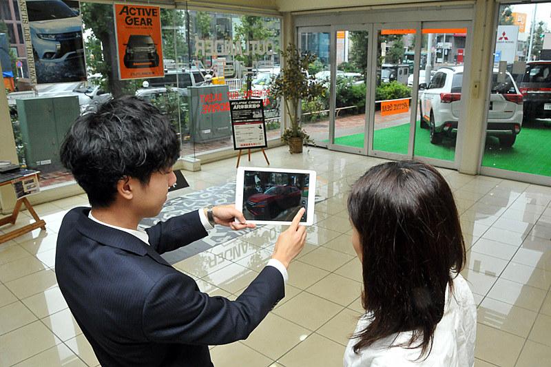 目黒店のスタッフの方にiPadの使い方を教えてもらう。と言っても難しい操作は必要なく、アプリを起動させて黒いシートにかざすだけでエクリプス クロスが現われる