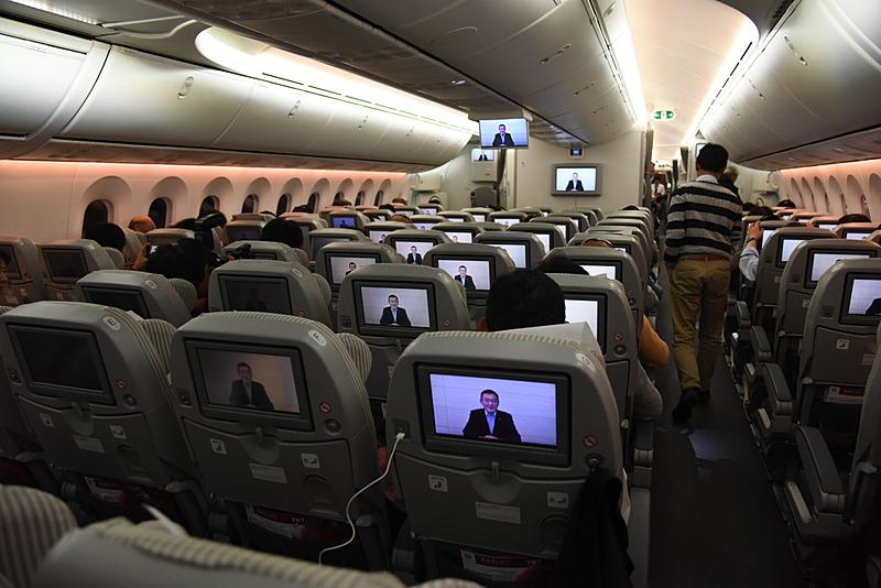 吉永社長の機内ビデオ挨拶が始まった。こちらはエコノミークラス。チャーター便ならではのプログラム