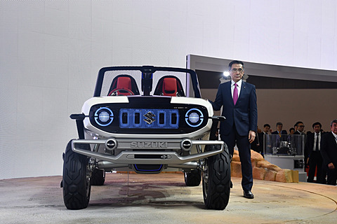 """【東京モーターショー2017】スズキのテーマは「""""ワクワク""""を、誰でも、どこへでも」。EVの4WDコンセプトカー「e-SURVIVOR」公開 スズキブースで開催されたプレスカンファレンスでスピーチを行なった、スズキ株式会社 代表取締役社長の鈴木俊宏氏とコンセプトモデルの「e-SURVIVOR」"""