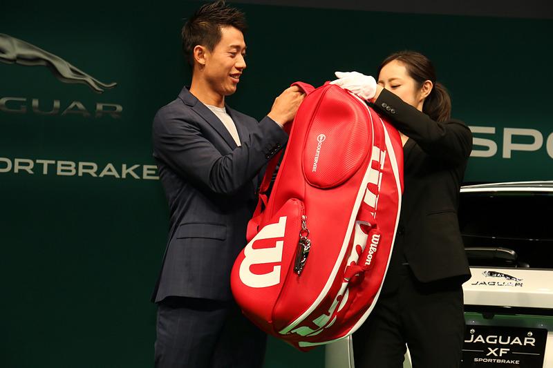 ラケットバッグを背負ってジャガーブランドチャームを紹介。ジャガーのブランドロゴが滑らかな金属で立体化されている