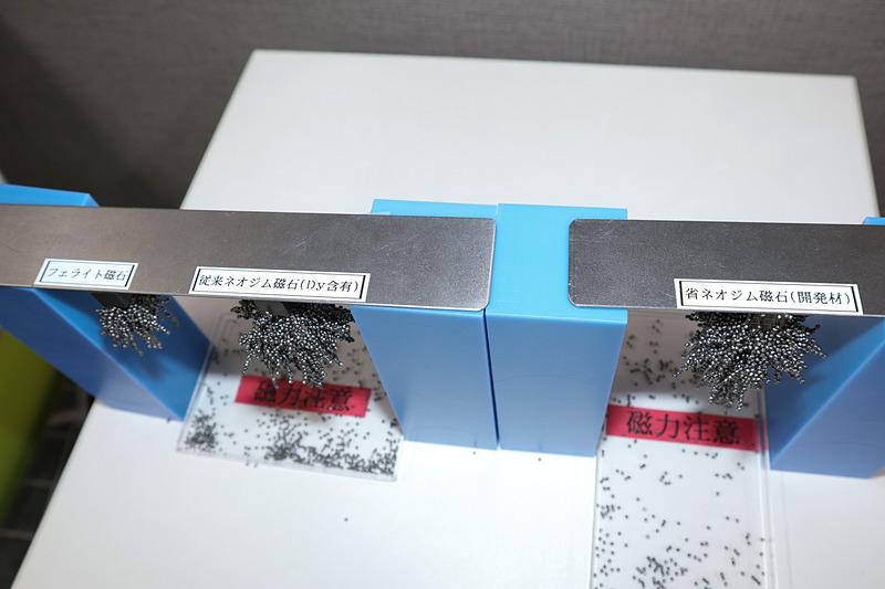 説明会で展示された磁力を比較する技術サンプル。左がフェライト磁石、中央が既存のネオジム磁石、右が省ネオジム耐熱磁石。細かな金属製の粒を使い、中央と右の磁石で大きな差がないとアピールした