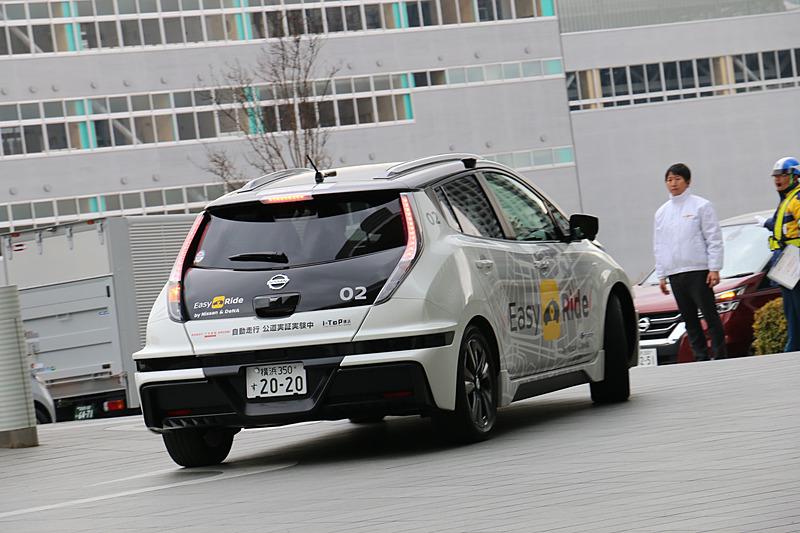 多数の報道陣が見守る中、実証実験用車両はEV(電気自動車)のリーフらしく静かにスタート。公道に出てすぐの交差点で赤信号を待ち、青信号を認識して横浜ワールドポーターズに向けて再スタートしていった