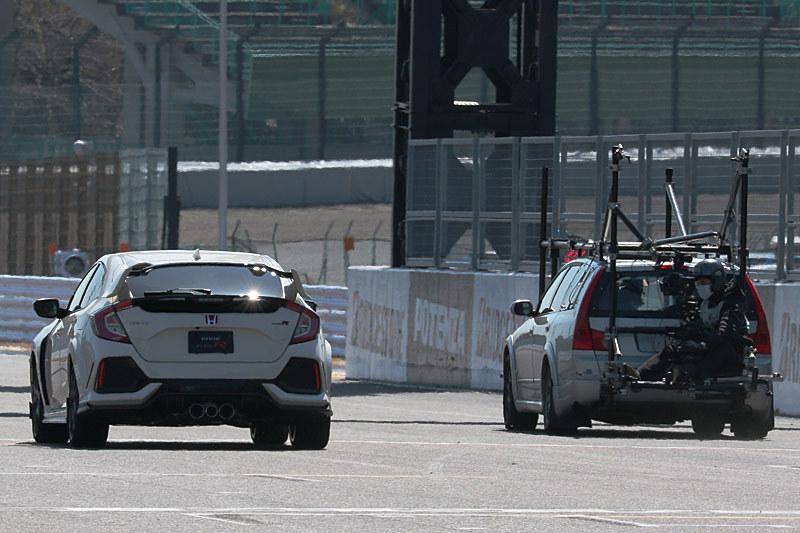 撮影用車両の背後に乗ったカメラマンがバトン選手を撮影した