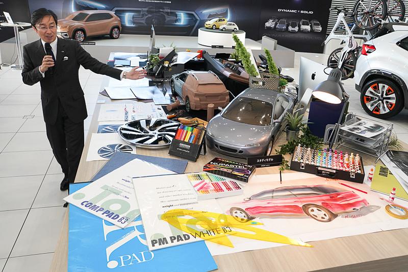 デザイン室のデスクをイメージした展示を石井デザイン部長が解説